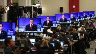 Republican Presidential candidate Sen. Ted Cruz (R-TX) is seen on a television screen as reporters watch the Republican Presidential debate sponsored by Fox News and Google at the Iowa Events Center on 28 January 2016 in Des Moines, Iowa