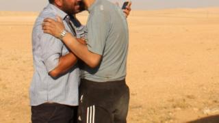 Dua pria Suriah berpelukan setelah memasuki area yang dikuasai pemberontak.