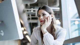 Una mujer contemplando, con expresión de aburrimiento, la pantalla de la computadora