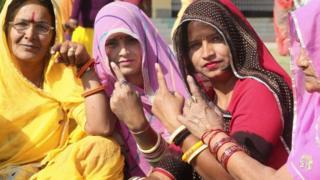 Mujeres en India muestran el dedo manchado con tinta indeleble que indica que votaron en las elecciones en Jaipur, diciembre 7, 2018