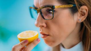 woman smelling a cut lemon