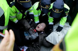 La policía subyuga a manifestantes anticorrupción frente a la casa de la depuesta presidenta de Corea del Sur, Park Geun-hye el 30 de marzo 2017, en Seúl.