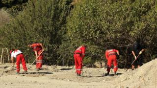 A South Yorkshire police officer (R) and members of the Greek rescue service (in red) excavate a site