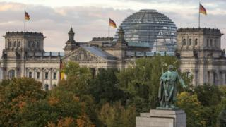 view of the Bundestag (German parliament) and its glass dome, with the monument to the soviet soldier in the foreground on German Unity Day (Tag der Deutschen Einheit) on October 3, 2017 in Berlin, Germany
