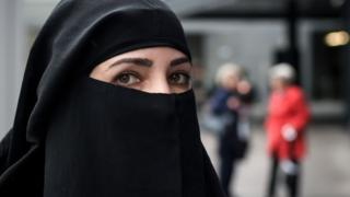A woman wearing a niqab looks on during a protest by a French-Algerian businessman and political activist, on October 3, 2018 in St. Gallen by following a massive vote in the Swiss northeastern canton of St. Gallen to prohibit all face-covering garments in public spaces.