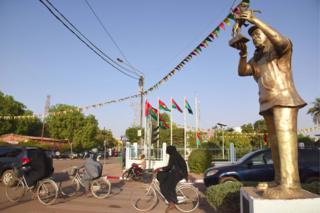 People drive past a bronze statue of Sembene Ousmane in street of Burkina Faso's capital Ouagadougou on February 22, 2019, on the eve of the opening of the Pan-African Film and Television Festival (FESPACO)