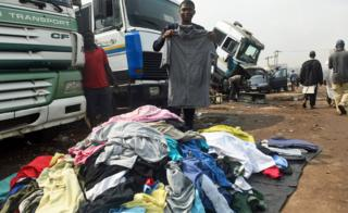 A boy holding up secondhand clothes for sale in Kara-Isheri in Ogun State, Nigeria - Tuesday 22 January 2019