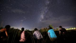 Five people crouch on the ground gazing up at a sky with meteors