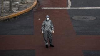A Chinese woman wears a protective suit in Beijing