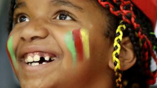 On Monday, a young fan of team Cameroon smiles ahead of a Women's preliminary volleyball match between agsinst Japan at the 2016 Summer Olympics in Rio de Janeiro, Brazil.