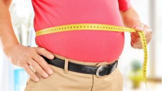 Un hombre de edad se mide el estómago