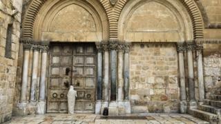 Christian pilgrim stands outside closed doors of Holy Sepulchre church in Jerusalem