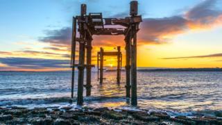 Sunrise through World War II pier head remains