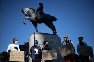 Demonstrators stand next to the statue of Louis Botha on horseback, the first prime minister of the Union of South Africa, during a demonstration calling for the removal of the statue in front of the South African Parliament, in Cape Town on June 16, 2020.