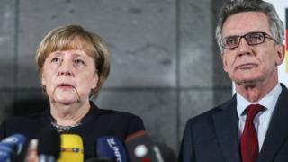 وزير الداخلية الألماني توماس دي ميتسيري مع أنغيلا ميركل