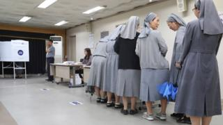 Nuns wait to vote at a polling station in South Korea