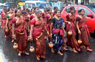 Despite heavy rain, men and women Kanwariyas march to a Shiva temple in Kolkata to offer the holy water from the Ganges.