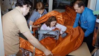صورة آيلين بيكر وهي تحيك جزءا من الواقي الحراري، والصورة معروضة بمركز جونسون الفضائي لناسا