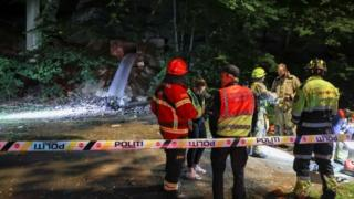 Emergency personnel are seen at the site where seven people have been found unconscious and sent to hospital after they were probably poisoned with carbon monoxide at a party in a bunker in Oslo