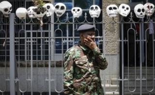 A police officer looks on in front of the mock skulls put on top of a fence guarding the Central Bank of Kenya during a protest against the politicians and leaders of war-torn South Sudan, in Nairobi, Kenya, 11 October 2018.