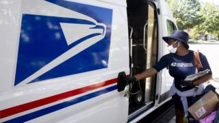 A postal workers closes a truck door