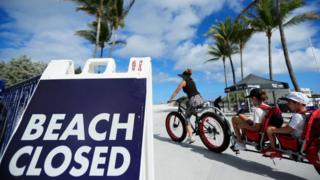 "A cyclist with a trailer for children passes a ""Beach Closed"" sign on the boardwalk on March 22, 2020 in Miami Beach, Florida"