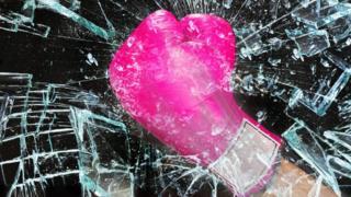 A boxing glove smashes through glass