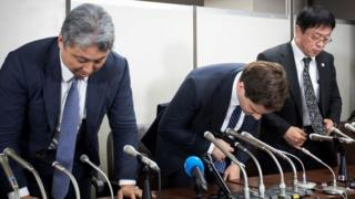 Mark Karpeles (centre) bows at a press conference after appearing in court.