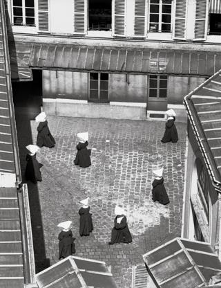 A group of nuns walk around a courtyard