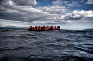 Migrants crowded on a flimsy boat at sea