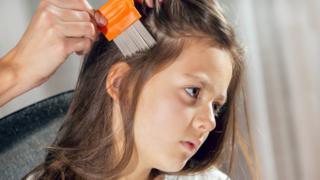 A girl being checked for head lice