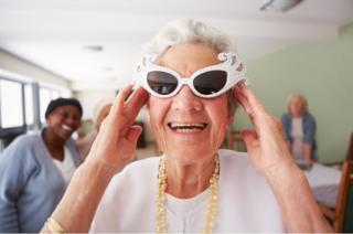 Mujer mayor con lentes de sol de diseño divertido sonriendo.