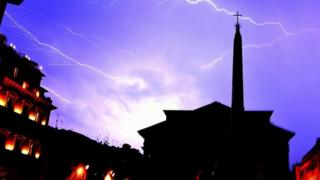 Lightning flashes across the sky over the Pantheon monument during a hailstorm in downtown Rome