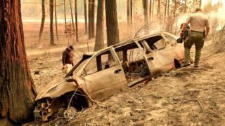 Помощники окружного шерифа обследуют сгоревший автомобиль - порой огонь распространяется так быстро, что люди не успевают эвакуировать свои машины