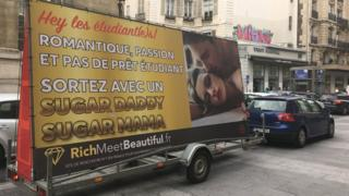 """A large billboard in French shows a couple apparently having sex in a high-end modelled photograph, accompanied by French text which reads: """"Hey students! Romance, passion, and no student loan, meet a Sugar Daddy or a Sugar Mama"""""""