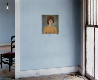 A blue wall with a portrait of a woman hanging on it.