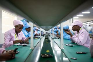 Factory workers assemble mobile phone parts at Uganda's first mobile phone factory which has been operating in Namanve, near Kampala, since August 2019.