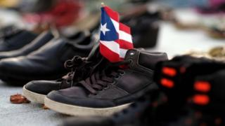 A Puerto Rican flag on a pair of shoes among hundreds displayed in memory of those killed by Hurricane Maria in front of the Puerto Rican Capitol, in San Juan (file photo)
