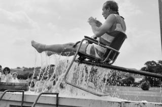 Director being dunked into pool in chair