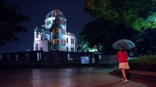 A pedestrian walking past the illuminated Atomic Bomb Done at night