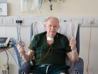 A patients holding his thumbs up