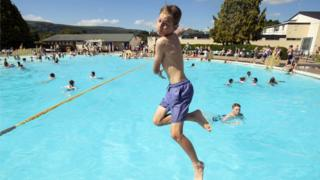 A boy jumps into the water at Ilkley outdoor pool and lido in west Yorkshire