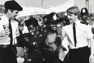 Two uniformed policemen dancing with two carnival goers at the Notting Hill Carnival, 1980s