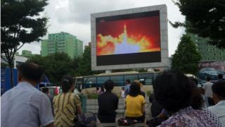 Pyongyang'da halk bir füze denemesinin görüntülerini izlerken.