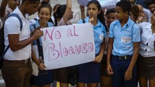 """Estudiantes en La Habana sostienen un cartel con la leyenda """"No al bloqueo""""."""