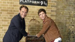 Jude Law and Eddie Redmayne pose at Platform 9 and 3/4 at London King's Cross station