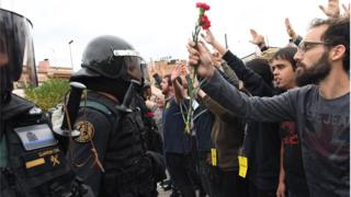 Crowds raise their arms up and a man holds red and pink flowers as police move in on members of the public gathered outside to prevent them from voting in the referendum at a polling station where the Catalonia President Carles Puigdemont will vote later today on October 1, 2017 in Sant Julia de Ramis