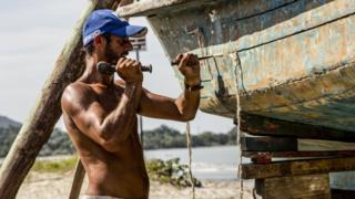 Wladimir, pescador de Ubatuba, calafetando seu barco