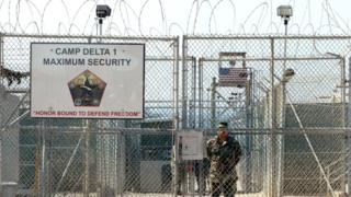 A U.S. Army soldier stands at the entrance to Camp Delta where detainees from the U.S. war in Afghanistan live April 7, 2004 in Guantanamo Bay, Cuba