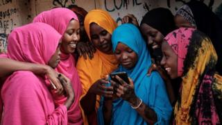 Young Somali refugee women look at a smartphone as they stand together at Dadaab refugee complex, in the north-east of Kenya, on April 16, 2018.